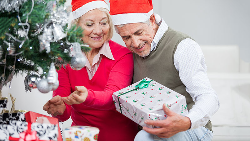 Smiling senior couple looking at present while decorating Christmas tree in house