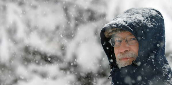 Man walking through snowstorm with a serious expression